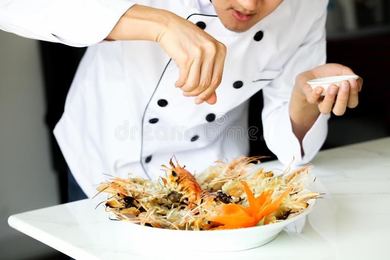 Chef sprinkling salt all over grilled prawns in the kitchen stock photos