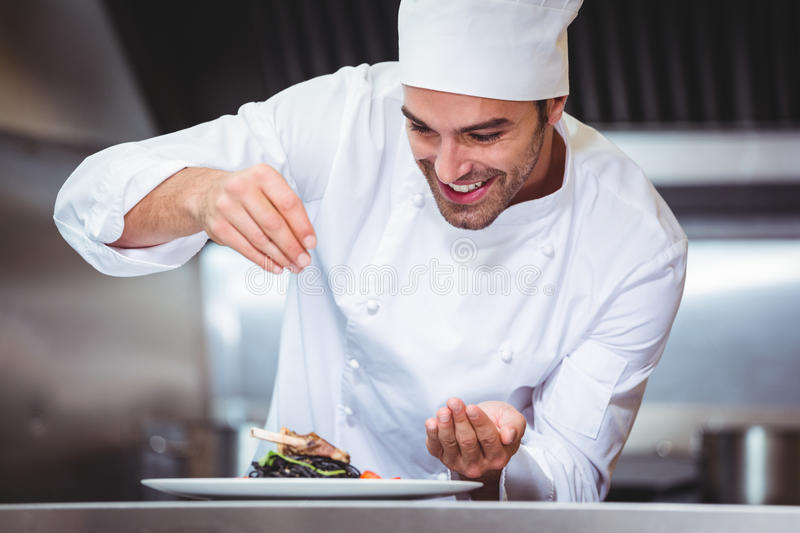 Chef sprinkling spices on dish. In commercial kitchen stock image