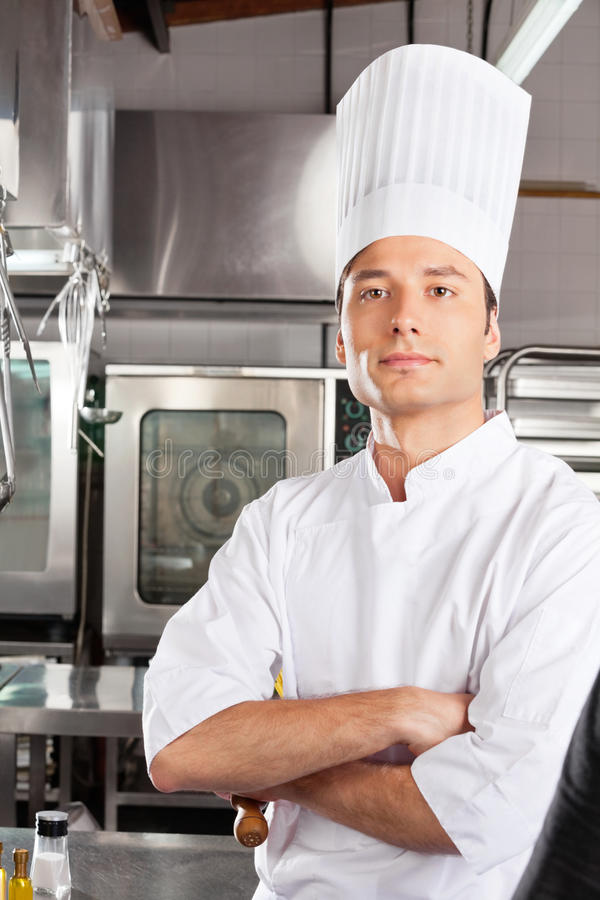 Chef Standing With Arms Crossed. Portrait of confident male chef standing with arms crossed in commercial kitchen stock images