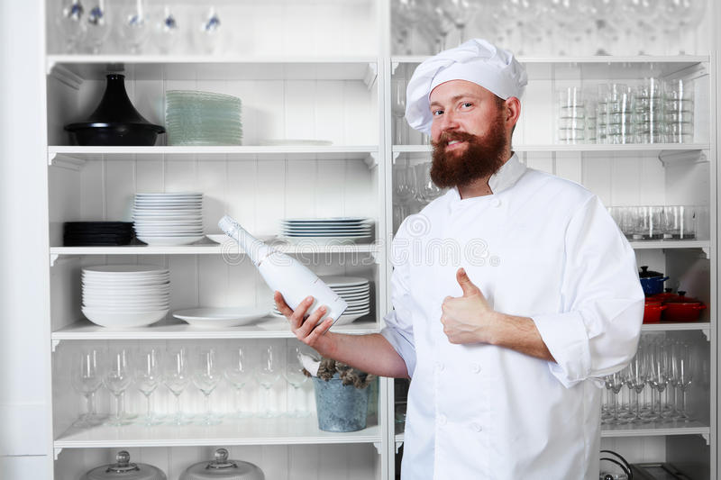 Download Chef Standing Next To Shelves With Dishes And Holding A Bottle Of Champagne For Their Visitors Stock Photo - Image of beverage, cuisine: 54213142
