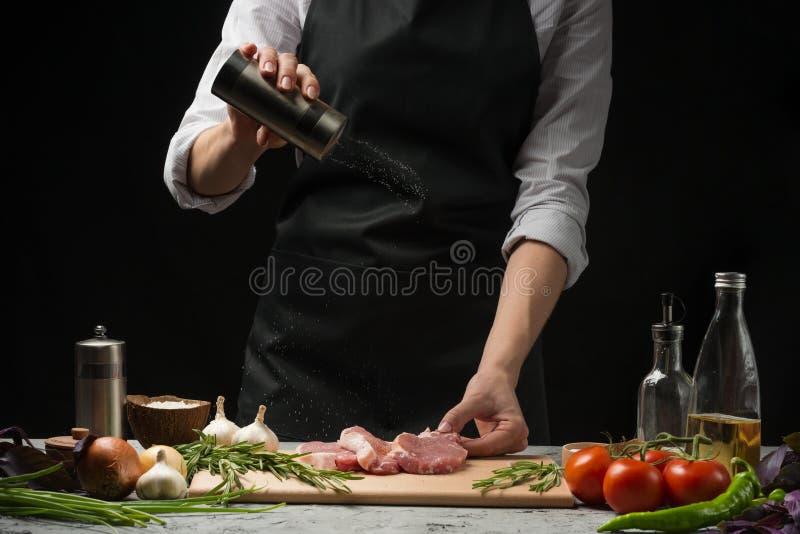 Chef, Steakfleisch in der Küche kochend und besprühen Salz auf einem Hintergrund des Gemüses, Tomate, Peperoni, Basilikum und Ros lizenzfreies stockbild