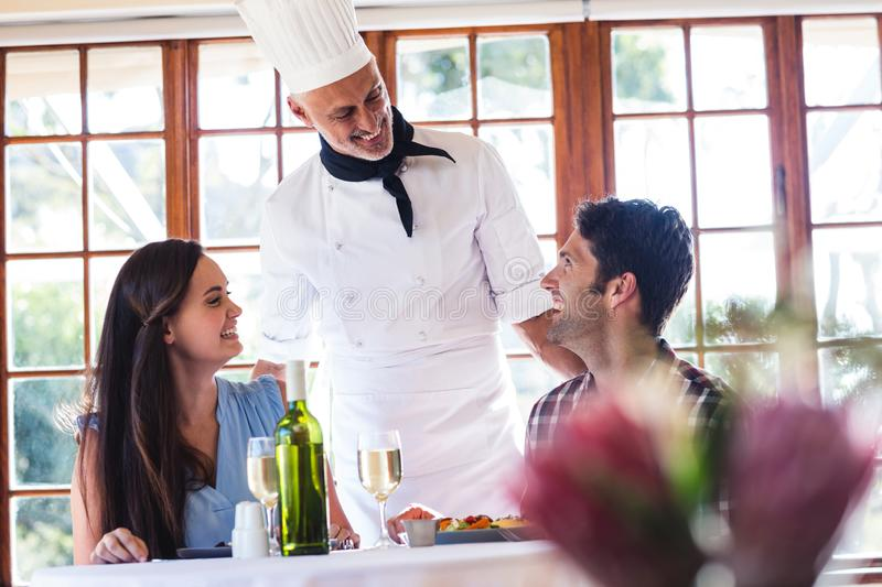 Chef talking to couple at restaurant stock photography