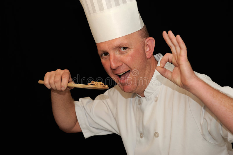 Chef tasting delicious food. A chef tasting delicious food with a wooden spoon royalty free stock photography