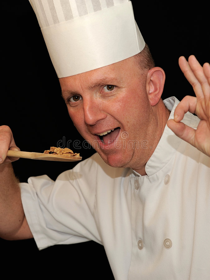 Chef tasting food. Chef in white uniform tasting food and giving ok signal stock photo