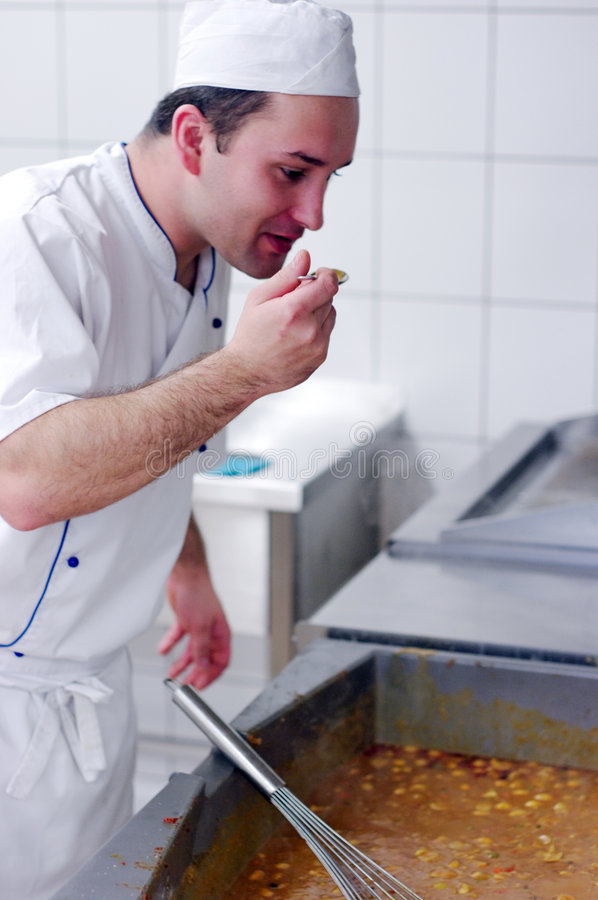 Chef tasting food. A chef working in an industrial kitchen, standing at large oven, tasting his freshly prepared food, seems to be satisfied with the results stock images