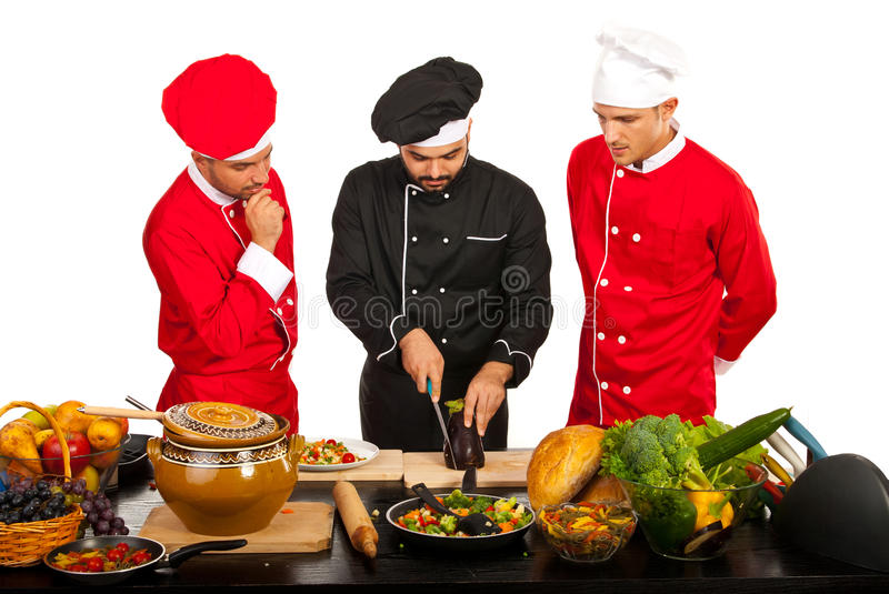Chef teacher with students in kitchen. Chef teacher with students teaching in kitchen royalty free stock photos
