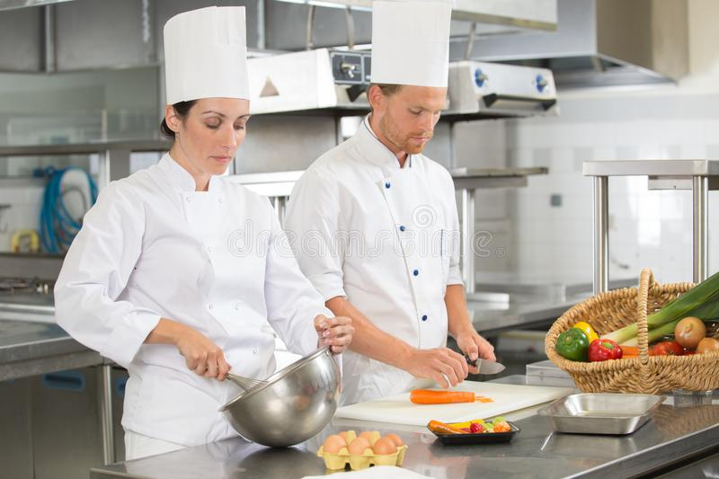 Chef teaching colleague how to slice vegetables in kitchen royalty free stock image