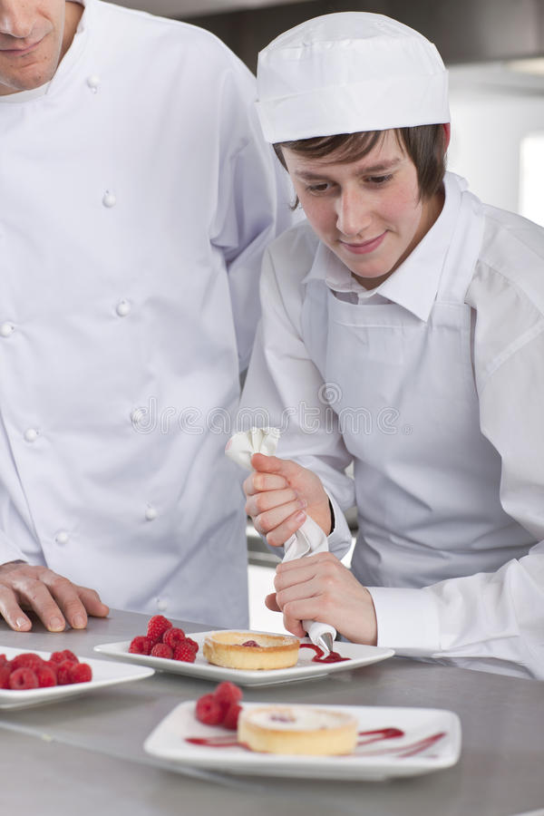 Chef teaching trainee how to garnish gourmet dessert in commercial kitchen royalty free stock photography