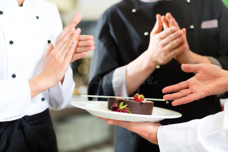 Chef team in restaurant kitchen with dessert royalty free stock image