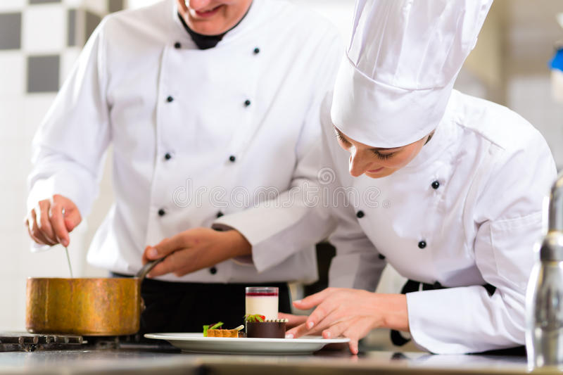 Chef team in restaurant kitchen with dessert. Working together royalty free stock image