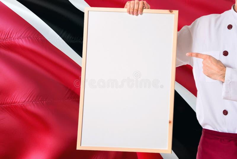 Chef tenant le menu vide de tableau blanc sur le fond de drapeau de Trinidad And Tobago Faites cuire l'uniforme de port dirigeant photos stock