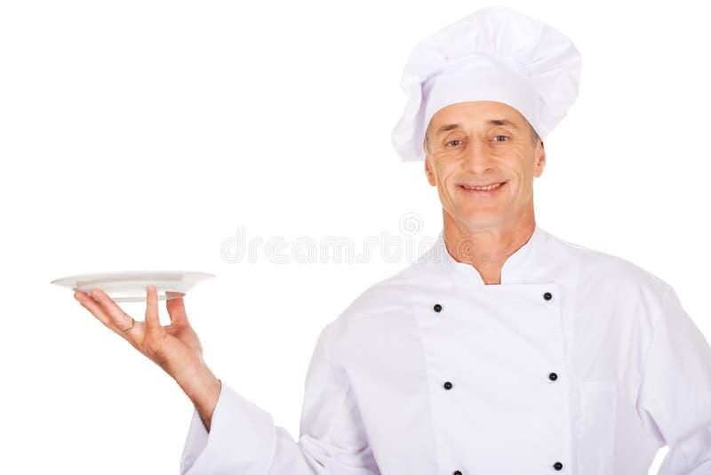 Chef tenant le plat blanc de porcelaine image stock