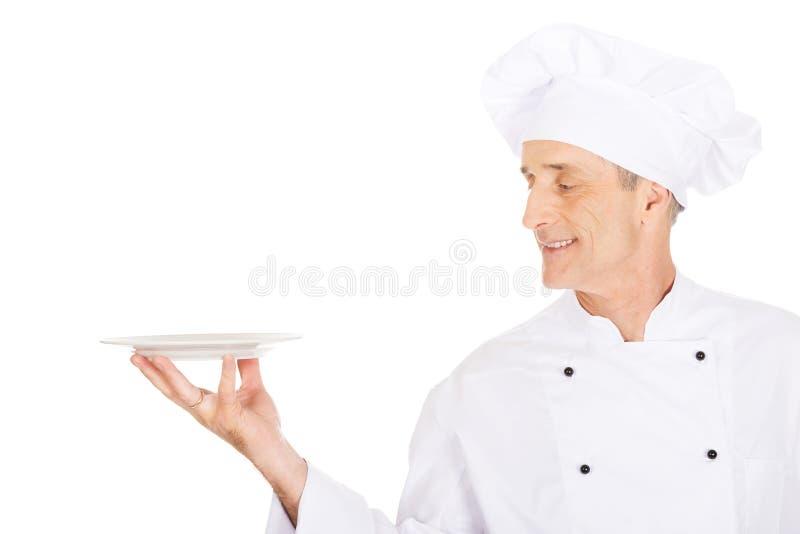 Chef tenant le plat blanc de porcelaine images stock