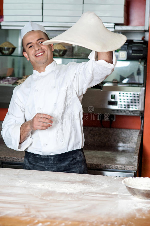 Chef throwing the pizza base dough stock photography