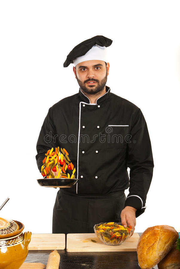 Chef tossing macaroni. With tomatoes in kitchen stock images
