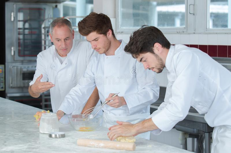 Chef and trainees in restaurant kitchen royalty free stock images