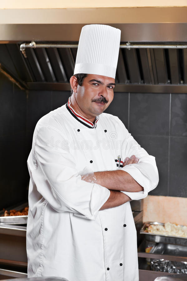 Chef in uniform at kitchen royalty free stock photography