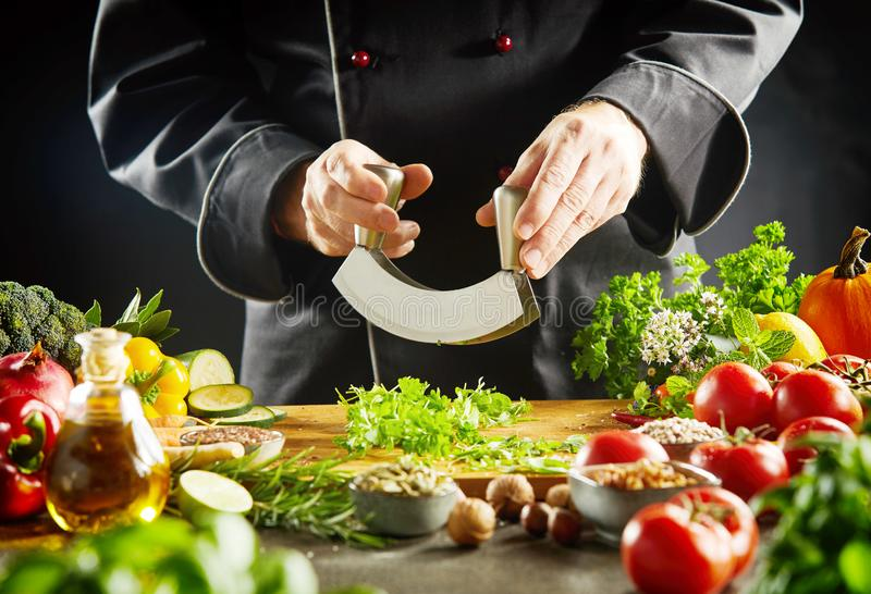 Chef using a mezzaluna knife to chop herbs stock photography