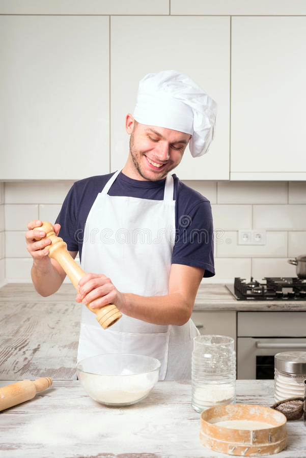 Chef using pepper mill in kitchen royalty free stock photos