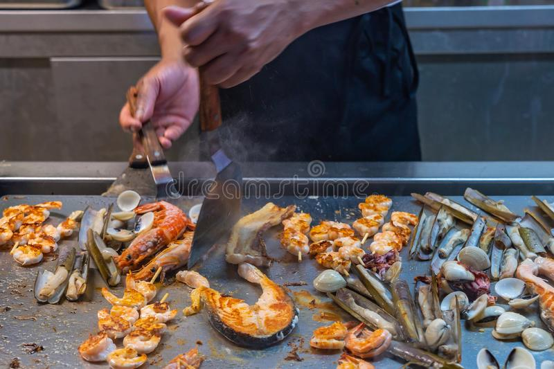 Chef using spatula frying assortment of seafood in restaurant`s kitchen royalty free stock photos