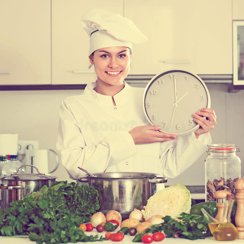 Chef with vegetables and clock. Portrait of professional happy young chef with vegetables and clock royalty free stock images
