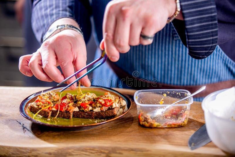 Chef verziert die Sandwiche des strengen Vegetariers mit gebackenem Gemüse und Käse auf gebratenem Handwerksbrot Vorlagenklasse i stockfoto