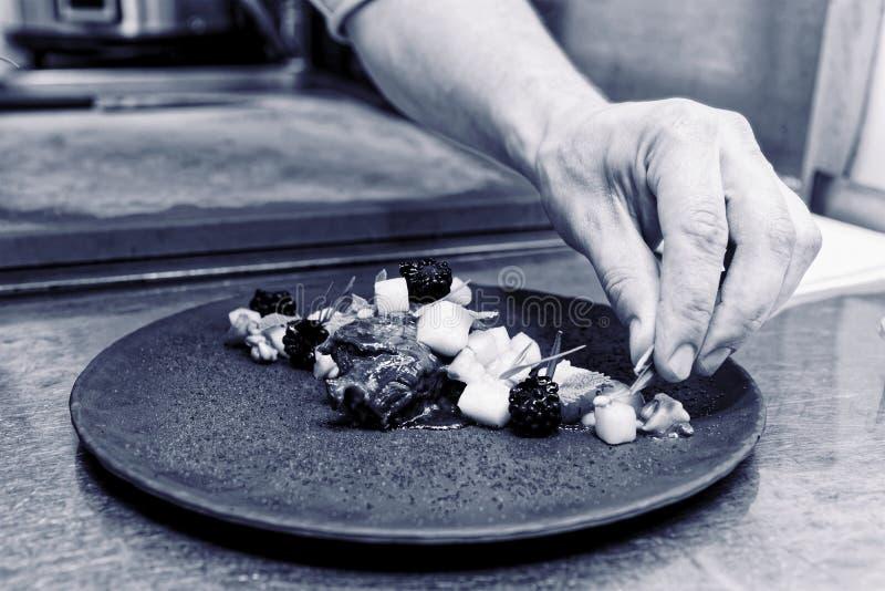 Chef verziert gedämpfte Kalbfleischbacken mit Kräutern und Beeren, zu lizenzfreie stockbilder