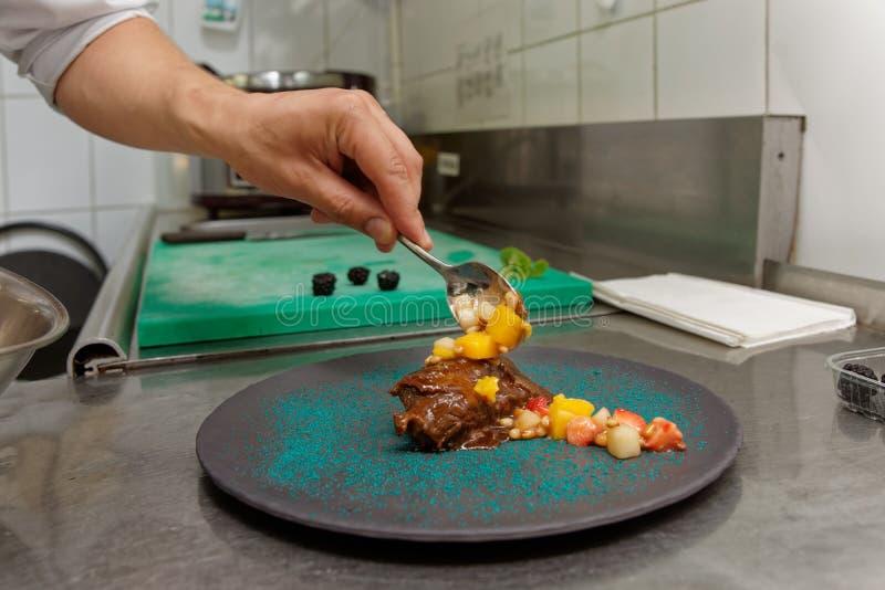 Chef verziert gedämpftes Kalbfleischfleisch mit Soße, Handelsküche stockfoto