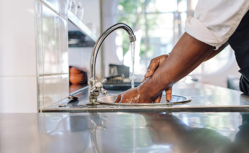 Chef washing his hands in commercial kitchen royalty free stock image