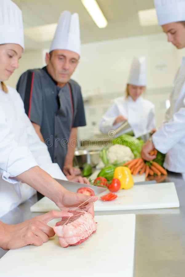 Chef watching student tie joint meat. Chef watching student tie joint of meat royalty free stock photo