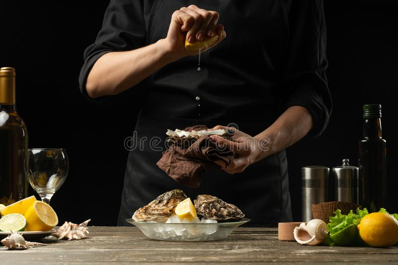 Chef watering raw oyster with lemon juice, with dry Italian wine, for cooking and cooking on a black background, Concept menu, royalty free stock photos
