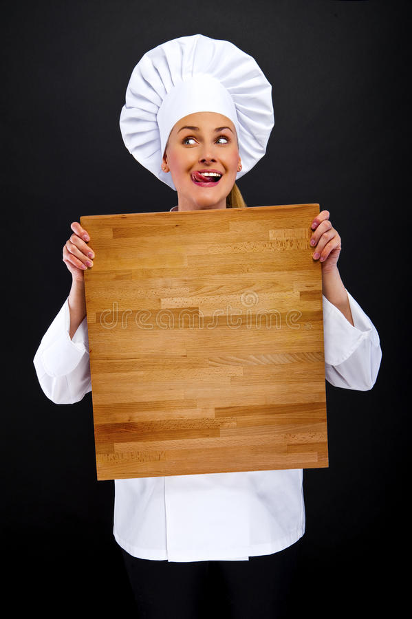 Chef woman on dark background in shock behind wooden board stock image