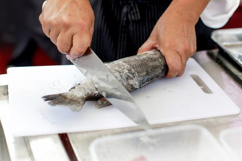 Chef at work,  chef filleting fish at the kitchen, Chef in restaurant kitchen filleting fish. Chef at work, chef filleting fish at the kitchen, Chef in royalty free stock images