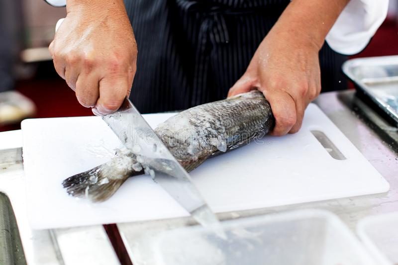 Chef at work, chef filleting fish at the kitchen, Chef in restaurant kitchen filleting fish. Background royalty free stock photos