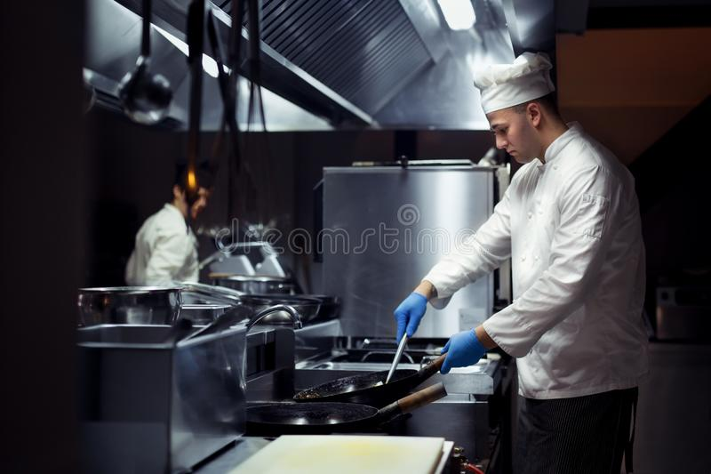 Chef working on the kitchen. Young chef working on the kitchen stock photo