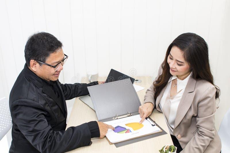 Chefaffärsman som talar med affärskvinnan på kontor arkivfoto