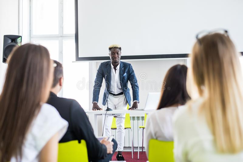 Chefe afro-americano de sorriso do homem que fala à equipe do negócio na sala de conferências Conferência de negócio Reunião de n fotografia de stock