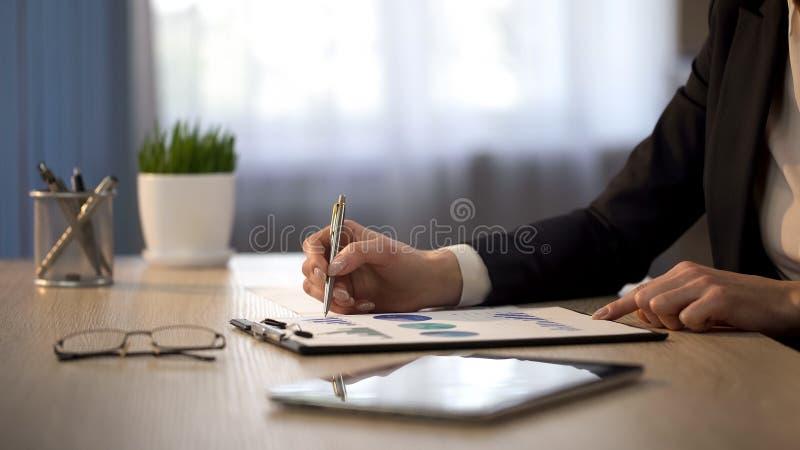 Chefe da senhora que olha gráficos estatísticos, verificação da revisão de empréstimo, equilíbrio financeiro imagens de stock royalty free