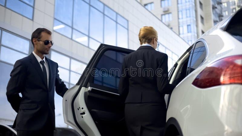 Chefe de espera do motorista pessoal no parque de estacionamento, ajudando à obter no carro imagens de stock
