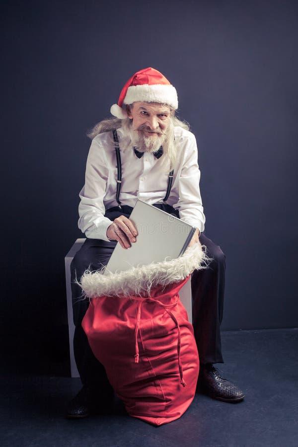 Chefe de Santa Claus que puxa o portátil do saco do presente fotos de stock