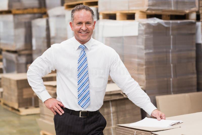 Chefe de sorriso que inclina-se na pilha de caixas imagem de stock