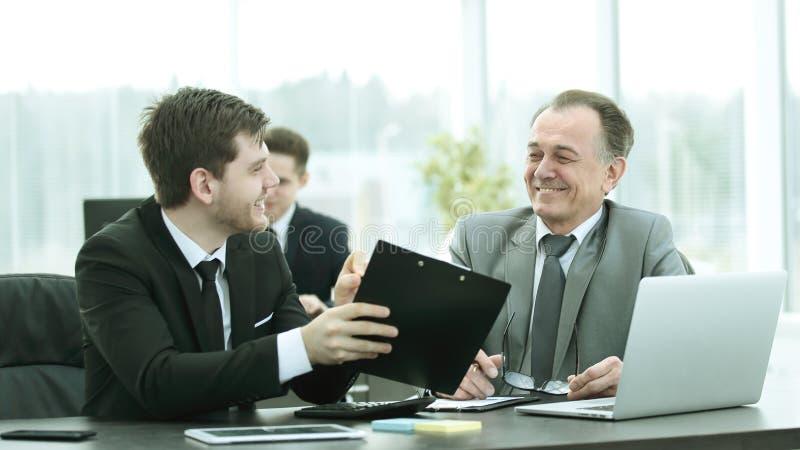 Chefe e empregado que discutem o original que senta-se na mesa no escritório fotografia de stock royalty free
