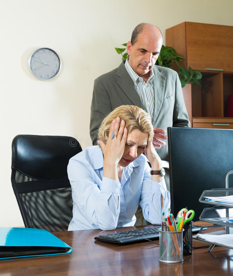 Chefe e secretário irritados no escritório imagem de stock