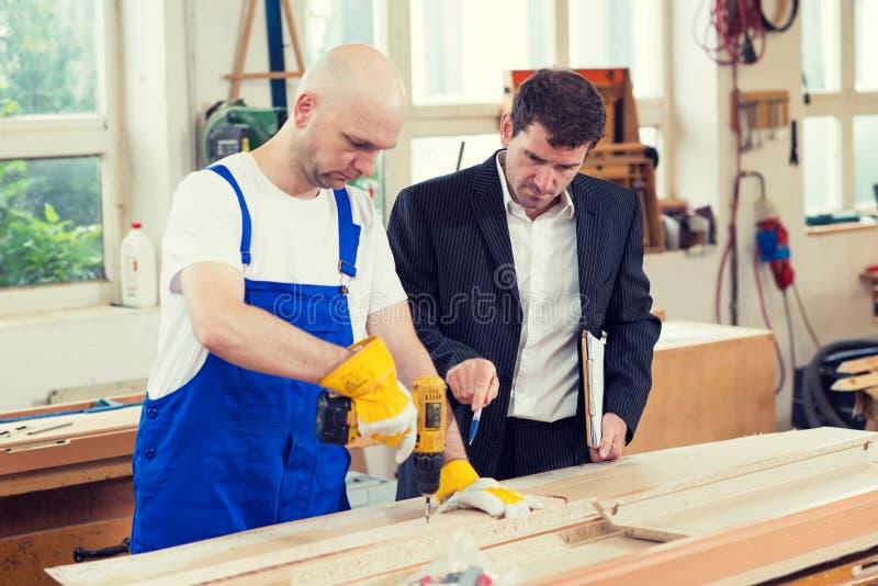 Chefe e trabalhador em uma oficina do ` s do carpinteiro foto de stock