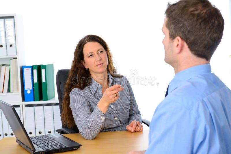 Chefe fêmea na conversação séria com caixeiro imagem de stock