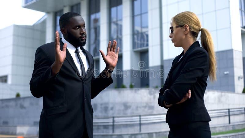 Chefe fêmea que ofende o empregado afro-americano, homem que tenta justificar seus acontecimentos fotografia de stock royalty free