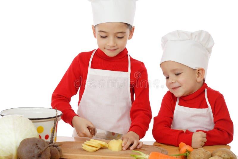 Chefe-fogões pequenos de sorriso na mesa fotografia de stock royalty free