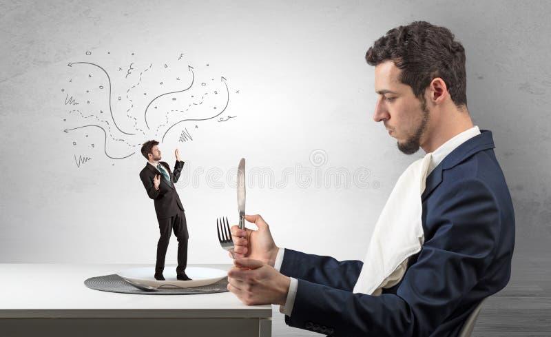 Chefe grande que come o homem de negócios pequeno fotografia de stock royalty free