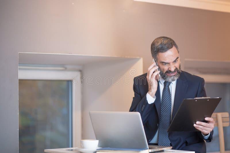 Chefe irritado que grita em seu empregado sobre o telefone fotos de stock royalty free