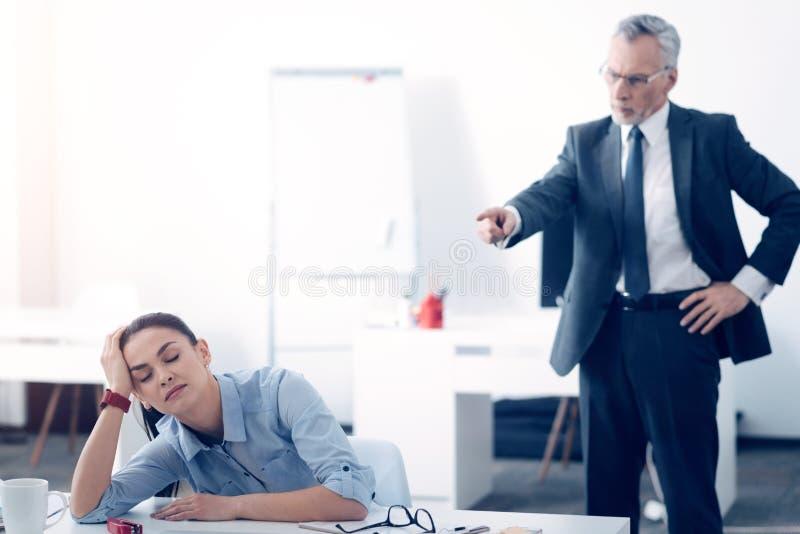Chefe irritado que grita no trabalhador de escritório fêmea cansado fotografia de stock